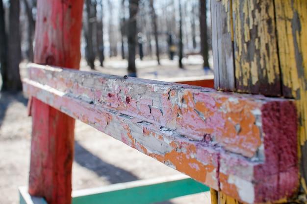 Structures en bois avec peinture colorée qui s'écaille sur le terrain de jeu