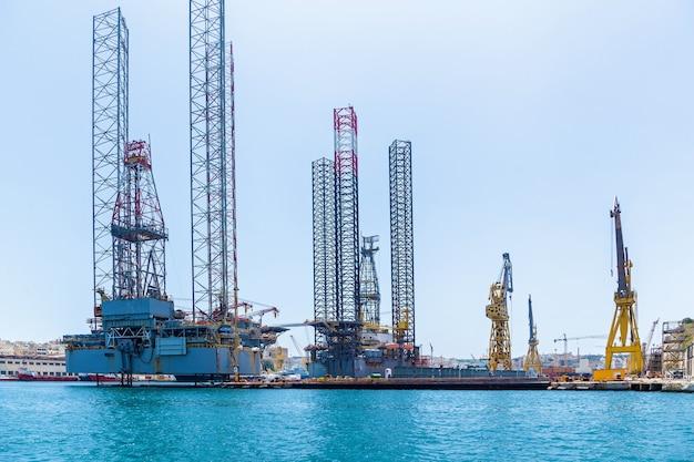 Des structures avec des équipements pour le forage de puits de pétrole sont situées dans la mer près d'un rivage de malte
