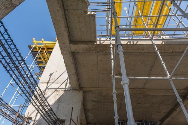 Structures métalliques en béton du bâtiment en construction. échafaudages et supports. vue de dessous