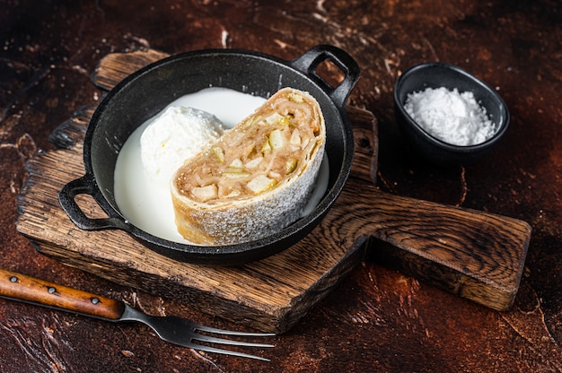 Strudel apfelstrudel à la cannelle, sucre en poudre et glace à la vanille dans une casserole. fond sombre. vue de dessus.