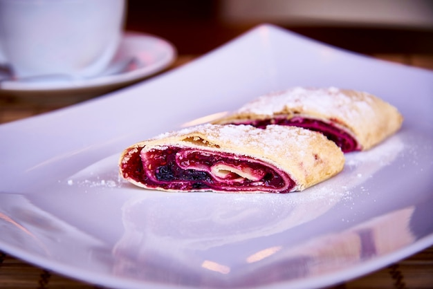 Strudel appétissant avec des baies sur une assiette blanche avec de la poudre et une tasse sur un gros plan de soucoupe.