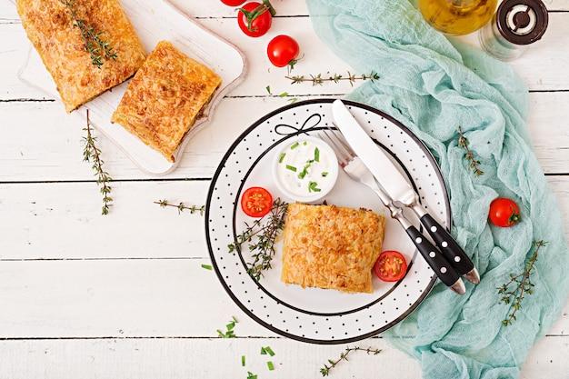 Strudel appétissant avec du boeuf haché, des oignons et des herbes. mise à plat. vue de dessus
