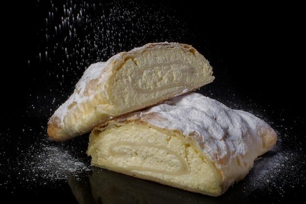 Strudel au fromage cottage saupoudré de sucre en poudre coupé en gros plan sur fond noir