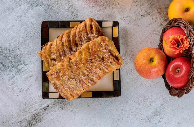 Strudel aux pommes sur une assiette carrée avec des pommes.