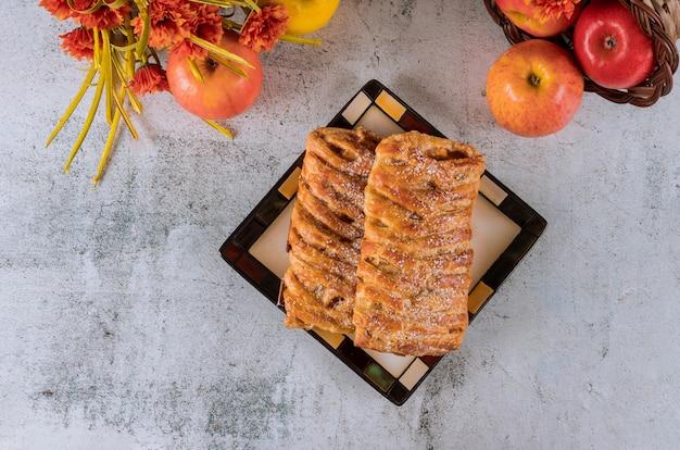 Strudel aux pommes et à la cannelle avec des fleurs et des pommes.