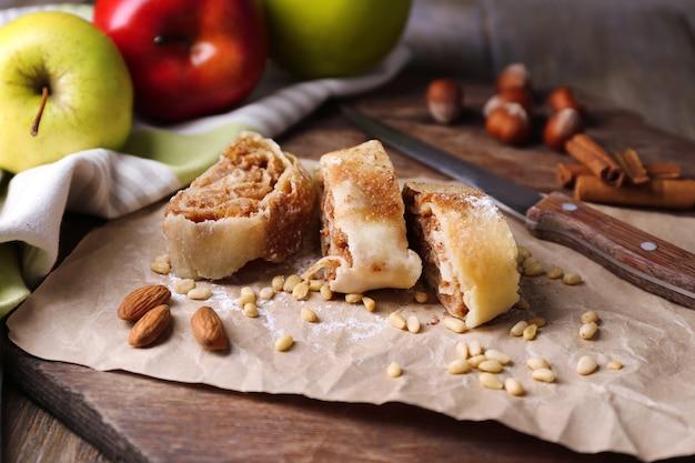 Strudel aux pommes fait maison savoureux sur une serviette en papier, sur une table en bois