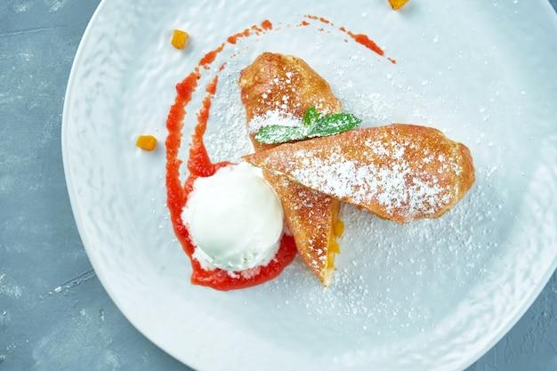 Strudel aux pommes avec glace et confiture rouge dans une assiette blanche. pâtisseries autrichiennes
