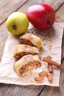 Strudel aux pommes maison savoureux sur une serviette en papier sur fond de bois