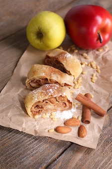 Strudel aux pommes maison savoureux sur une serviette en papier, sur fond de bois