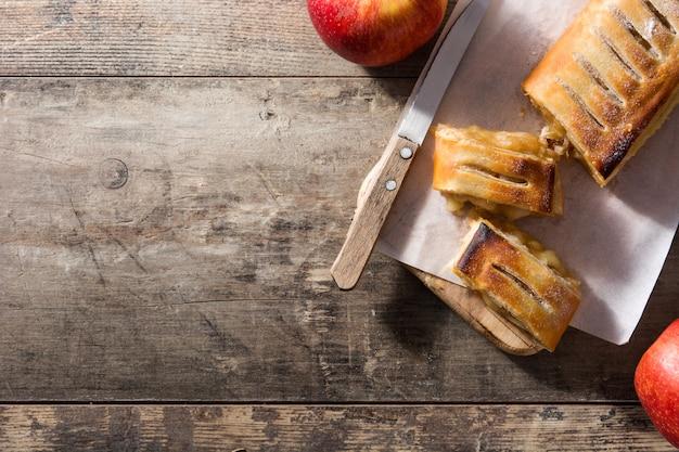 Strudel aux pommes maison traditionnelle sur une table en bois. vue de dessus