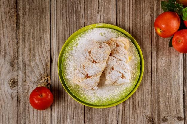 Strudel aux pommes avec pommes rouges fraîches sur table en bois