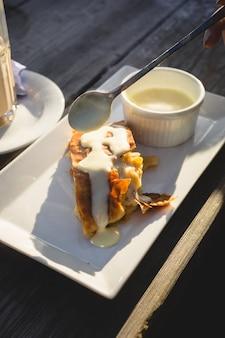 Strudel aux pommes avec sauce à la vanille sur table en bois