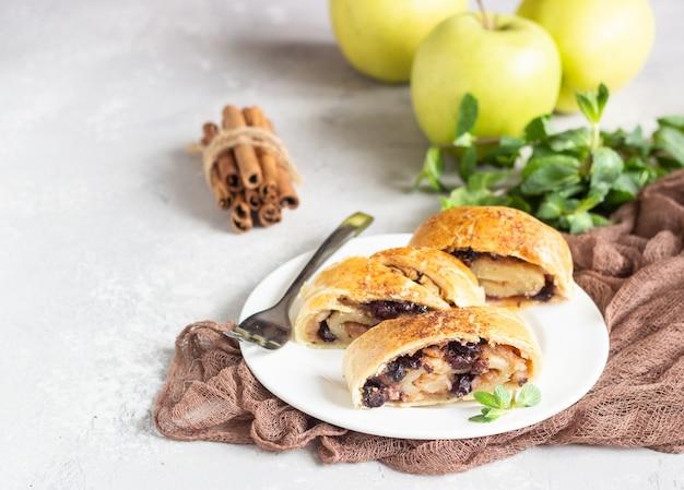 Strudel aux pommes traditionnel avec raisins secs et cannelle sur béton gris