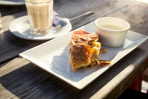 Strudel aux pommes traditionnel avec sauce à la vanille sur une vieille table en bois