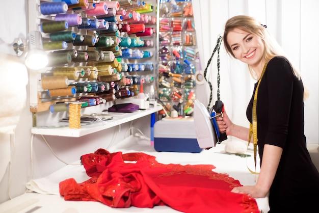 Studio de création d'atelier sur la couture. la créatrice passe le tissu à la vapeur avant de couper les pièces