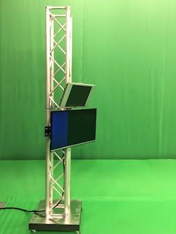 Studio d'enregistrement et de diffusion vidéo vert vide moderne avec écran tv canal et des stands métalliques