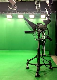 Studio d'enregistrement et de diffusion vidéo vide vert moderne avec écran tv canal et des stands métalliques, texte prompteur, s'allume