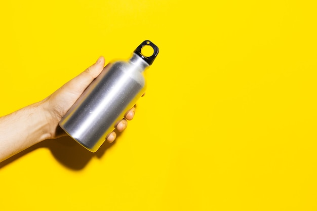 Studio gros plan portrait de main masculine tenant une bouteille d'eau thermo en aluminium éco réutilisable isolé sur une surface jaune avec espace de copie.