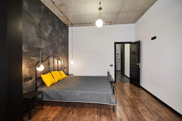Studio de luxe avec une disposition libre dans un style loft dans des couleurs sombres et jaunes