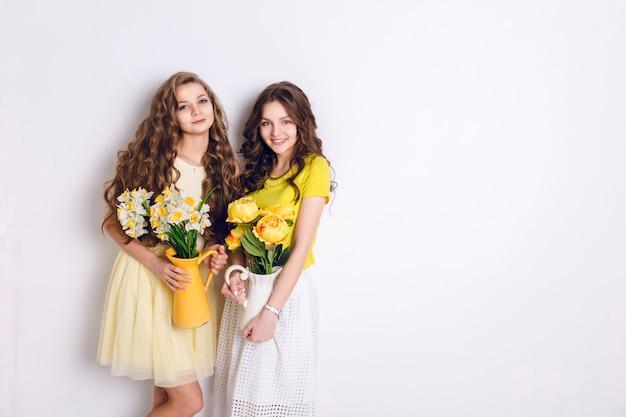 Studio photo de deux filles souriantes debout. une fille blonde et une fille brune tiennent des vases avec des fleurs. brunette porte une jupe blanche et un t-shirt jaune, et une fille blonde porte une robe jaune