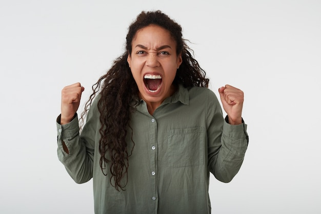 Studio photo de femme aux cheveux longs bouclés à la peau foncée, levant les poings avec enthousiasme tout en hurlant de colère, vêtue d'une chemise verte tout en posant sur fond blanc