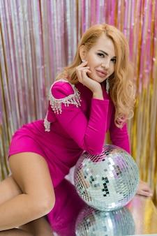 Studio photo de femme blonde glamour en robe rose de luxe posant avec boule disco