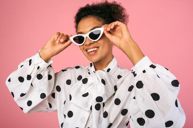 Studio photo de femme noire africaine en robe élégante et lunettes de soleil blanches