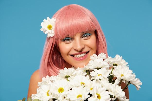 Studio photo de jeune femme aux cheveux rose assez romantique avec maquillage festif posant dans des fleurs blanches sur fond bleu, regardant positivement la caméra avec un sourire charmant