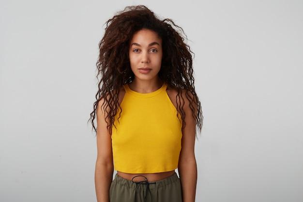 Studio photo de jeune femme brune bouclée aux cheveux assez sombre avec un maquillage naturel regardant calmement la caméra et en gardant les mains baissées tout en posant sur fond blanc