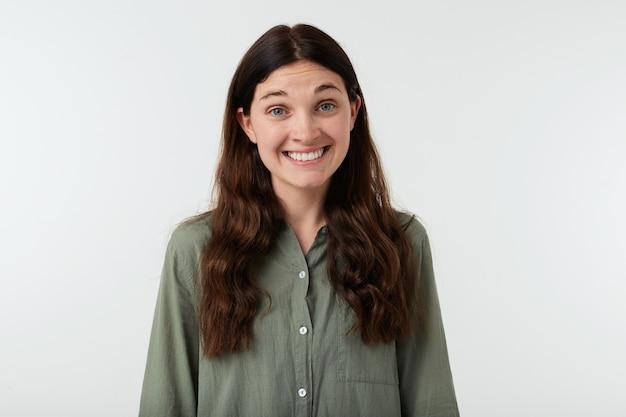 Studio photo de jeune femme brune heureuse avec de longs cheveux ondulés