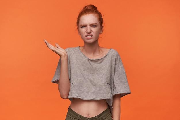 Studio photo de jolie jeune femme portant ses cheveux foxy en noeud, fronçant le visage avec la moue et soulevant la paume vers le haut, debout sur fond orange en t-shirt gris et short vert