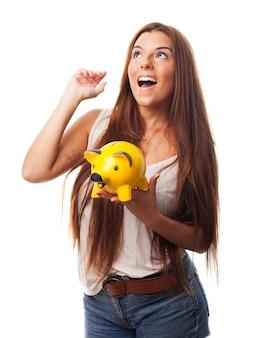 Studio portrait de jeune fille tenant moneybox jaune.