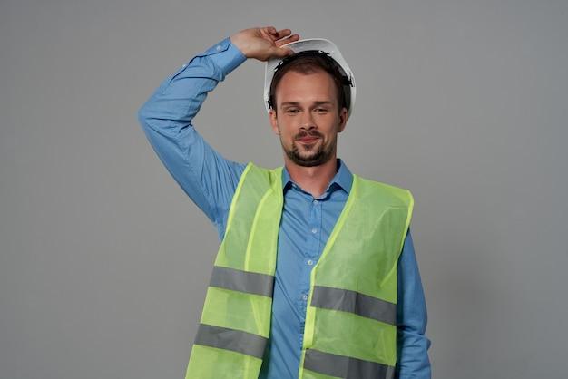 Studio professionnel d'émotions de gilet réfléchissant de constructeur masculin posant