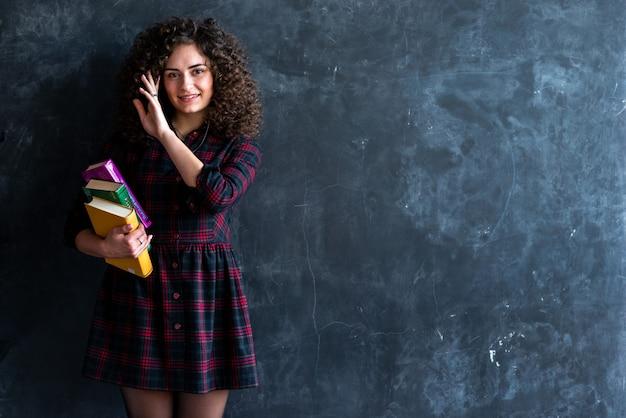 Studio shoot d'une souriante fille brune bouclée avec un livre dans ses mains