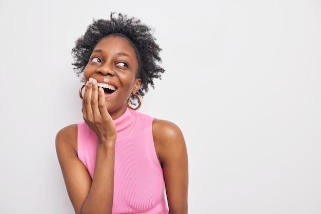 Studio shot of happy cury haired woman rit joyeusement couvre la bouche avec la main concentrée avec une expression insouciante de côté