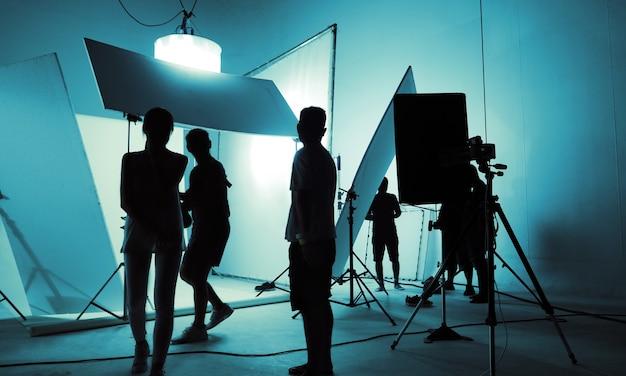 Studio de tournage pour photographe et directeur artistique créatif avec l'équipe de production installant un flash d'éclairage et un phare led sur un trépied et un équipement professionnel pour la séance photo de modèle portrait