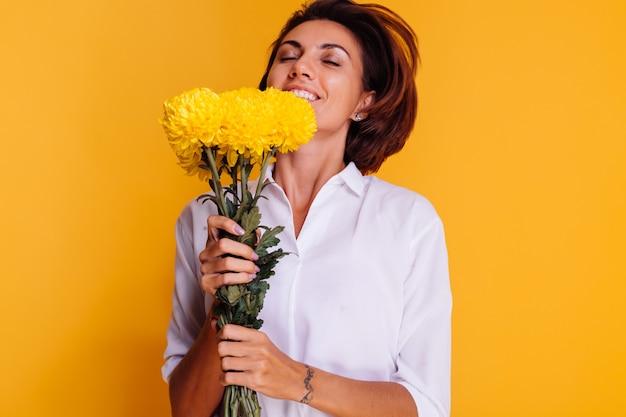 Studio tourné sur fond jaune heureux femme caucasienne cheveux courts portant des vêtements décontractés chemise blanche et pantalon en jean tenant bouquet d'asters jaunes