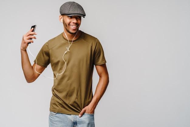 Studio tourné jeune homme afro-américain, écouter de la musique avec des écouteurs