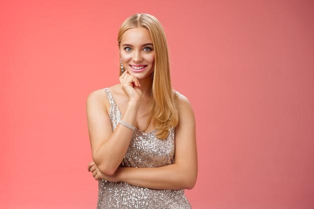 Studio tourné jolie femme européenne blonde tendre et joyeuse dans une élégante robe argentée scintillante touche le menton souriant, un ami d'écoute intéressé parle conversation pendant la fête, fond rouge.