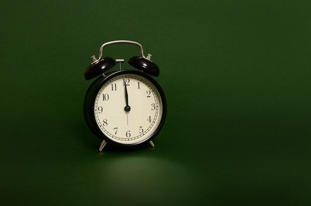 Studio tourné avec des ombres douces d'un réveil noir avec minuit sur le cadran de l'horloge isolé sur fond vert foncé avec espace de copie pour l'annonce. il est temps de célébrer noël et le nouvel an