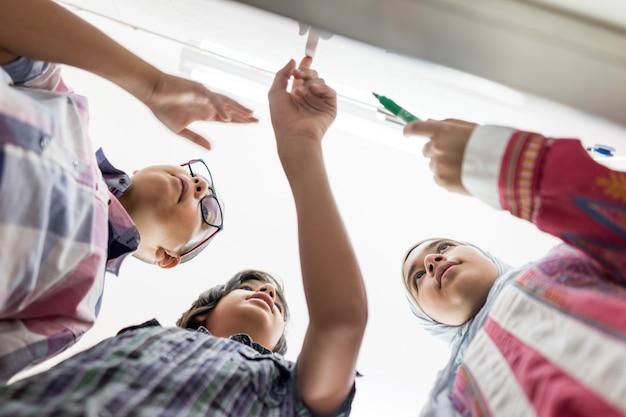 Des studnets discutant d'une question mathématique sur une carte blanche en classe