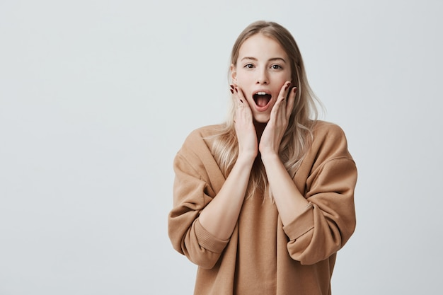 Stupéfaite, une femme blonde stupéfaite garde la bouche largement ouverte