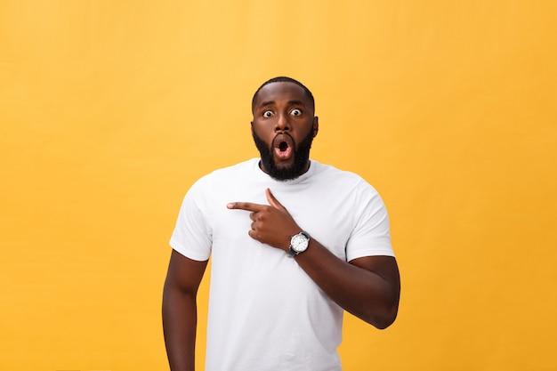 Stupéfié jeune hipster afro-américain portant un t-shirt blanc tenant par la main dans un geste surpris