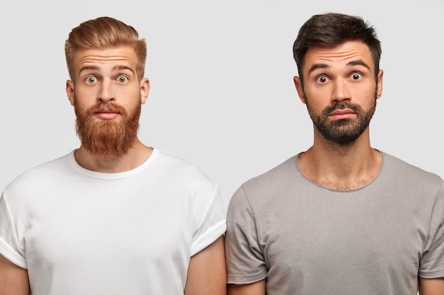 Stupéfiés et émotifs, de jeunes barbus étonnés que leur ami ait acheté une voiture chère. mâle gingembre avec expression stupéfaite et son frère posent ensemble contre un mur blanc. concept omg