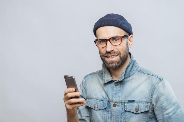 Stusio coup d'homme heureux barbu avec chaume tient un téléphone intelligent moderne dans les mains