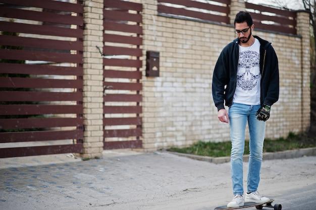 Style arabe homme à lunettes avec longboard longboard sur la route.