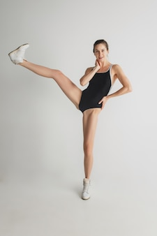 Style. belle jeune femme isolée sur fond gris studio. s'amuser, heureux, pleine longueur. danser, devenir fou, s'amuser. fille élégante en maillot de bain sportif noir. espace de copie.