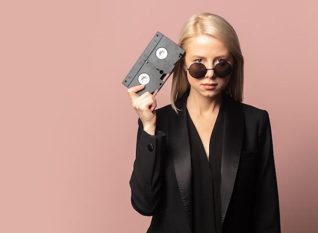Style blonde en blazer noir avec bande vhs sur fond rose