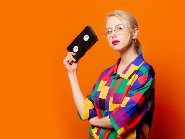 Style blonde en chemise des années 90 et lunettes avec type vhs sur orange