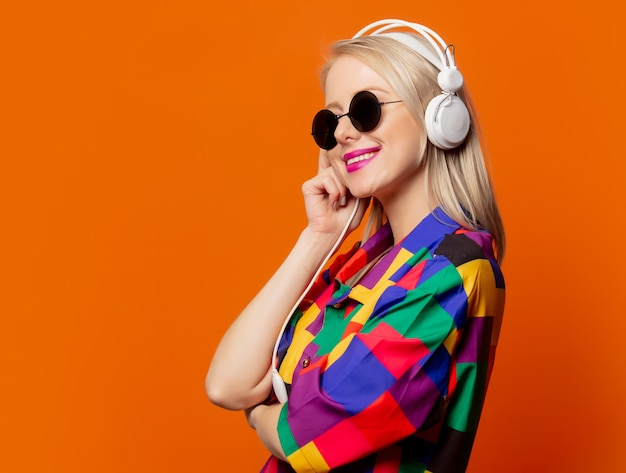 Style blonde dans des vêtements des années 90 avec des écouteurs sur orange